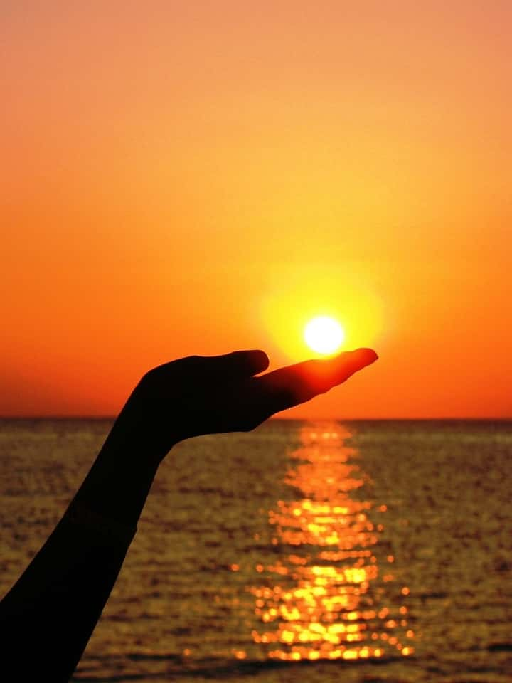 Picture is showing sunset and sea with hand reach out